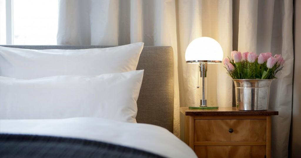 Bett mit stilvollem Nachttisch und Lampe in Ferienwohnung Herma